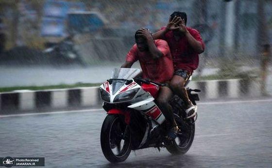 صحنه خنده دار دو موتور سوار برای در امان از باران +عکس